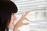 A young woman looking out through window blinds