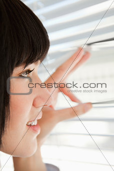Close up of a woman looking out through blinds