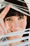 Close up of woman looking through blinds into the camera