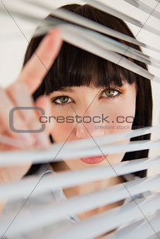 A woman looking through some blinds into the camera