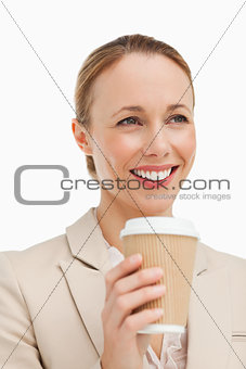 Woman in a suit holding a takeaway coffee