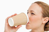 Close-up of a woman in a suit drinking a takeaway coffee