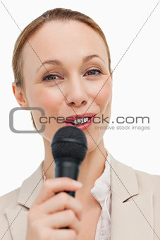 Portrait of a woman in a suit speaking with a microphone