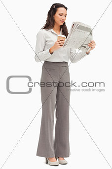 Employee reading the news with a coffee in the hand