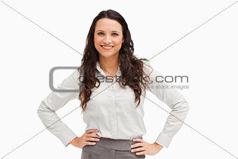 Portrait of a brunette businesswoman hands on hips smiling