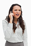 Close-up of a businesswoman grimacing while phoning
