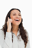 Pretty brunette laughing while phoning