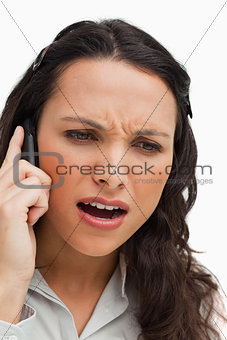 Close-up of a brunette frowning while phoning