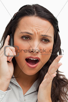 Portrait of a brunette shocked while using her mobile