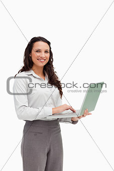 Portrait of a brunette standing while using a laptop