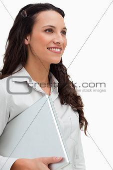 Close-up of a brunette standing while holding a laptop