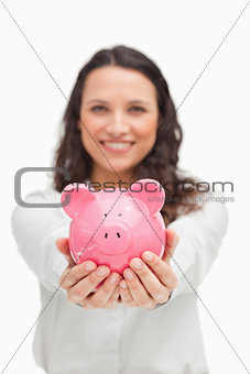 Brunette showing a piggy bank