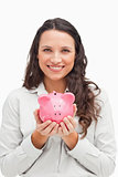 Brunette holding a piggy bank