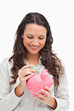 Brunette putting money in a piggy bank