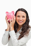 Portrait of a brunette shaking a piggy bank