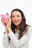 Brunette shaking a piggy bank