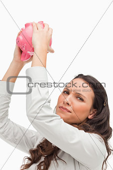 Portrait of a brunette holding an empty piggy bank