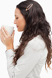 Profile of a brunette smelling a hot coffee