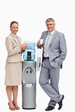 Portrait of business people smiling next to the water dispenser 