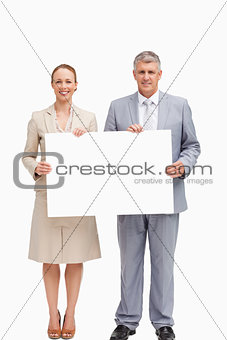 Business people smiling while holding a poster