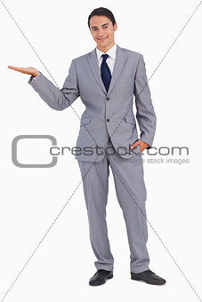 Smiling man in suit presenting with the hand