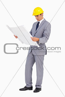 Man in a suit with safety helmet watching plans
