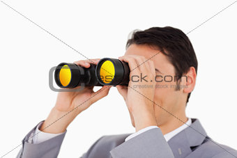 Man in a suit using binoculars