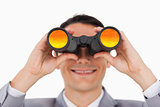Close-up of a smiling businessman using binoculars 