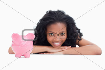 A smiling girl resting her head on her hands with a piggy bank i