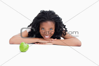 A smiling girl is resting her head on her hands with an apple in