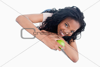 A young girl lying on the ground holding an apple