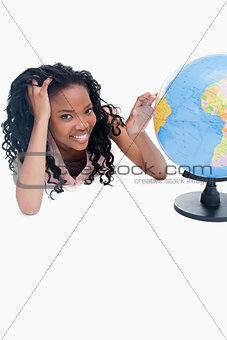 A young girl with her and on a globe