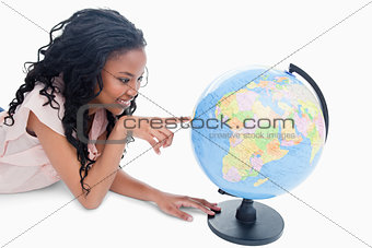 A young girl is pointing at a globe