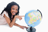 A young girl smiling at the camera has her finger on a globe
