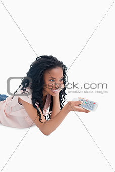 A young girl lying on the floor is holding a television remote c