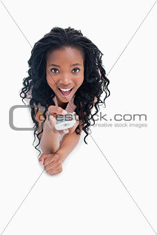 A surprised young woman is pointing a television remote at the c