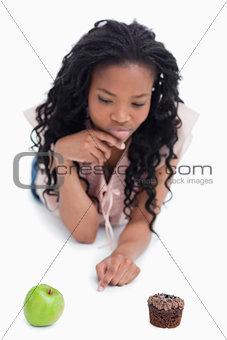 A woman choosing between an apple or a bun