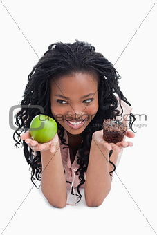 A smiling young woman is holding an apple and a bun on the palms