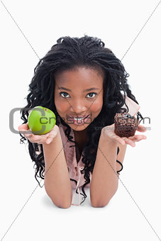 A young woman looking at the camera is holding an apple and a bu