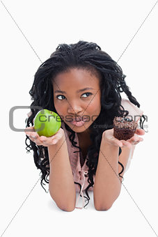 A woman holding an apple and a bun on her palms is thinking