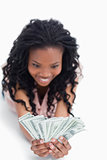 An excited young woman is holding American dollars in her hands