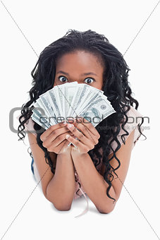 A woman is holding American dollars up to her face