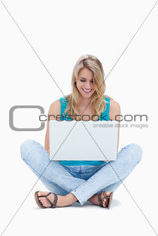 A woman is sitting on the ground looking at her laptop