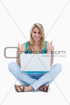 A woman with her thumbs up is sitting on the ground with a lapto