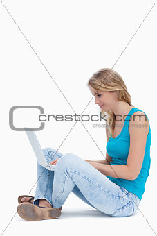 A side view of a woman sitting on the ground typing on a laptop
