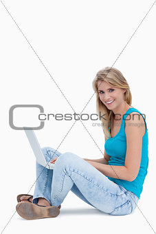 A woman smiling at the camera with a laptop on the leg