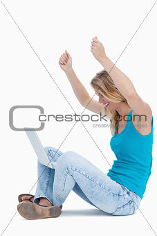 A woman has her arms in the air and a laptop between her legs