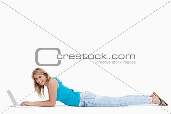 A woman smiling at the camera is lying on the ground typing on h