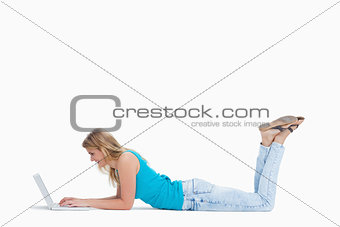 A woman lying on the floor with her legs up is typing on her lap