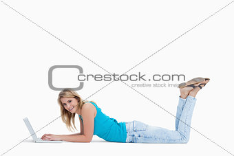 A smiling woman lying on the floor with her laptop